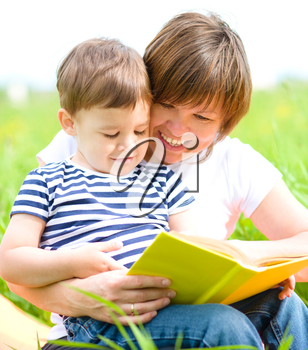 Mother is reading book for her child while sitting on a green grass outdoors
