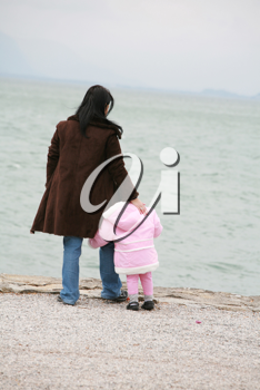 Mother and daughter looking the sea on winter