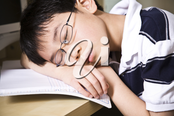 A shot of an asian student falling asleep while studying at home