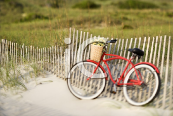 Red vintage bicycle with basket and flowers leaning against wooden fence at beach.