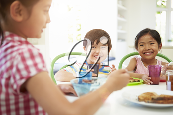 Three Asian Children Having Breakfast Together In Kitchen