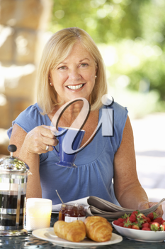 Senior woman eating breakfast outdoors