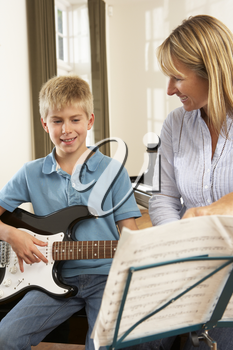 Boy playing electric guitar in music lesson