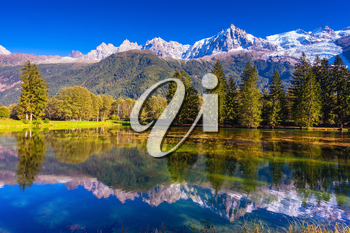 Early fall in Shamoni, Haute-Savoie. France. The snow-covered Alps and evergreen fir-trees are reflected in lake