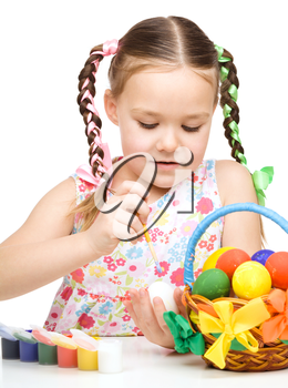 Little girl is painting eggs preparing for Easter, isolated over white