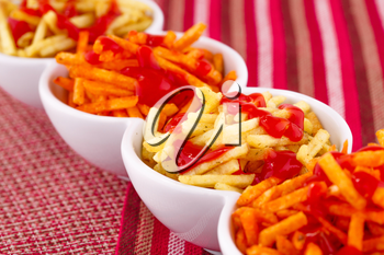 Potato chips with ketchup isolated on colorful tablecloth.