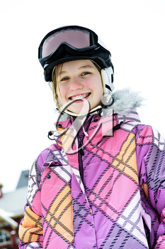 Portrait of happy teenage girl in ski helmet and goggles at winter resort