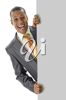 Image of joyful businessman peeping out of blank poster with your ad