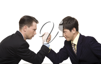 Two businessmen looking at each other seriously while doing arm wrestling